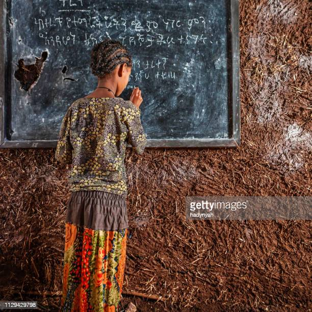 african little girl is learning amharic language - africa foto e immagini stock