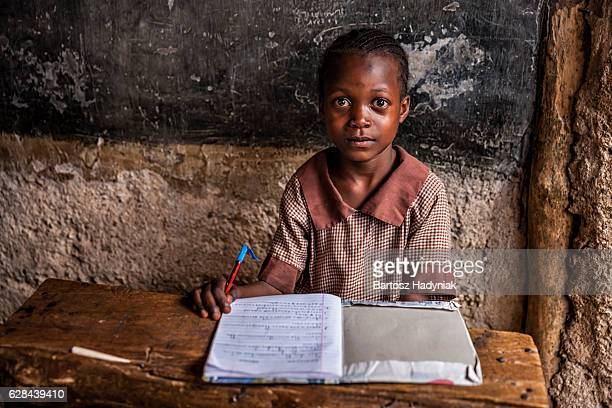 african little girl is learning english language, orphanage in kenya - human arm stockfoto's en -beelden