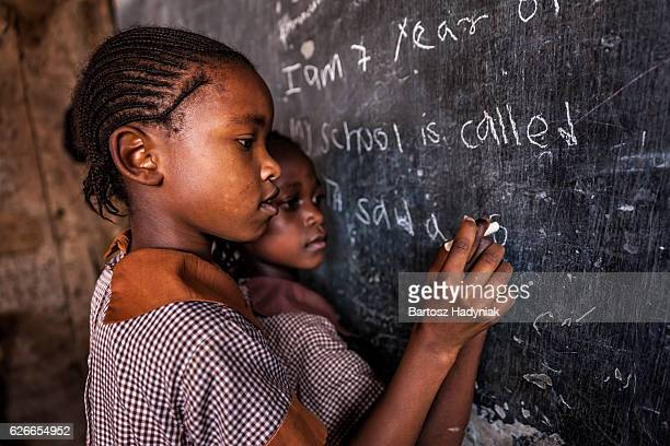 african little girls are learning english language, orphanage in kenya - afrika stockfoto's en -beelden