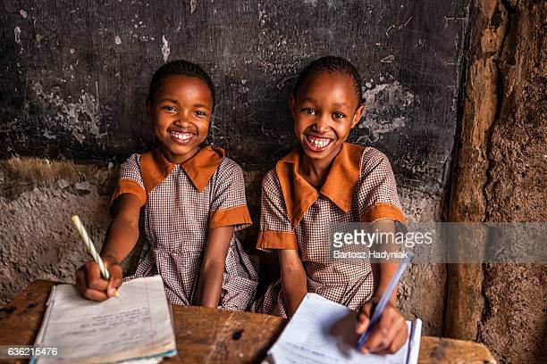 african little girls are learning english language, orphanage in kenya - armoede stockfoto's en -beelden