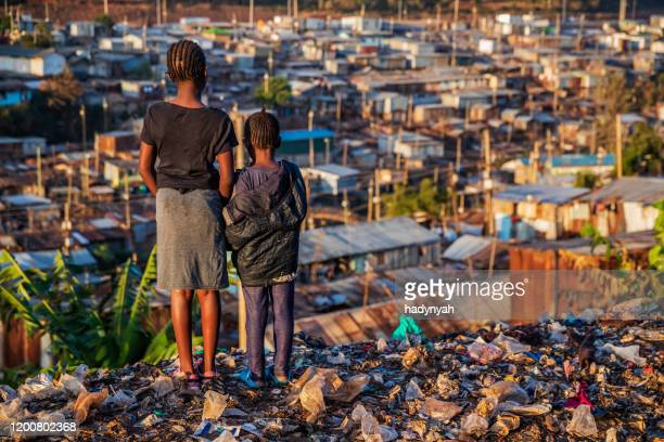 african little girls standing in trash and looking at kibera slum, kenya, east africa - poverty stock pictures, royalty-free photos & images