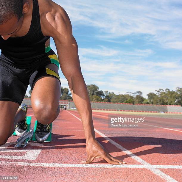 African male athlete in starting position on track