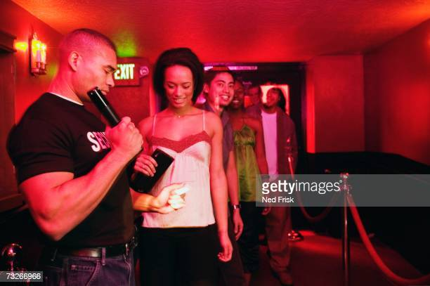 african male bouncer checking ids at nightclub entrance - doorman stock photos and pictures