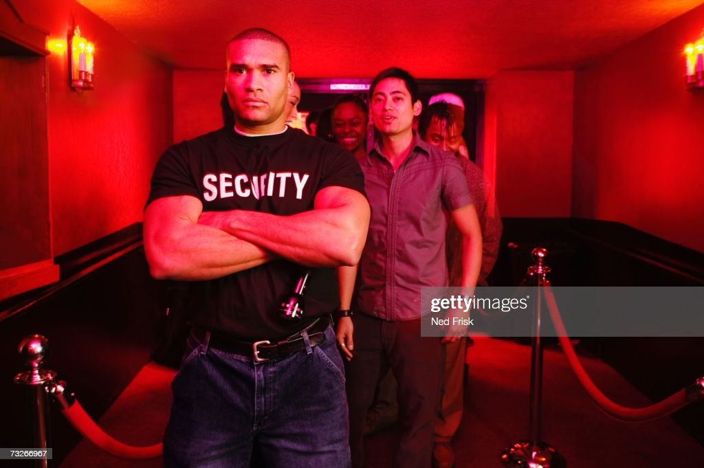 African male bouncer with arms crossed in front of line of people : Stock Photo