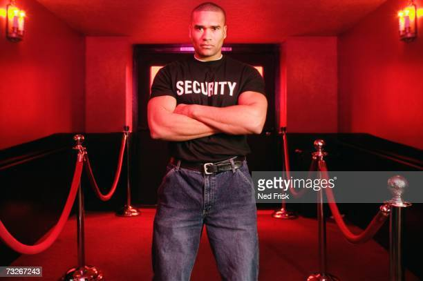 African male bouncer with arms crossed next to velvet ropes
