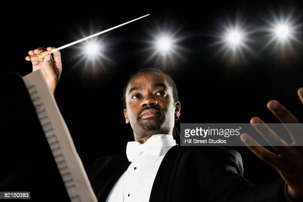 african male conductor holding baton - dirigent stock-fotos und bilder
