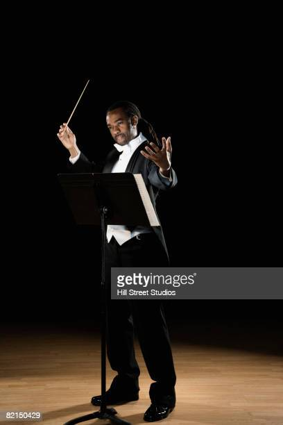 african male conductor holding baton - maestro stock photos and pictures