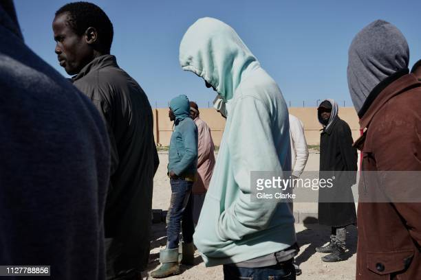 African male detainees at Qanfoodah Detention Center wait in line to be declared present at morning roll call on February 2,2019 in Libya. At the...