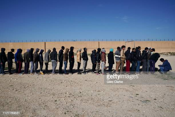 CENTER BENGHAZI LIBYA FEBRUARY 2 2019 African male detainees at Qanfoodah Detention Center wait in line to be declared present at morning roll call...