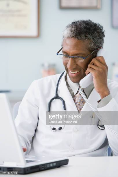 African male doctor talking on telephone