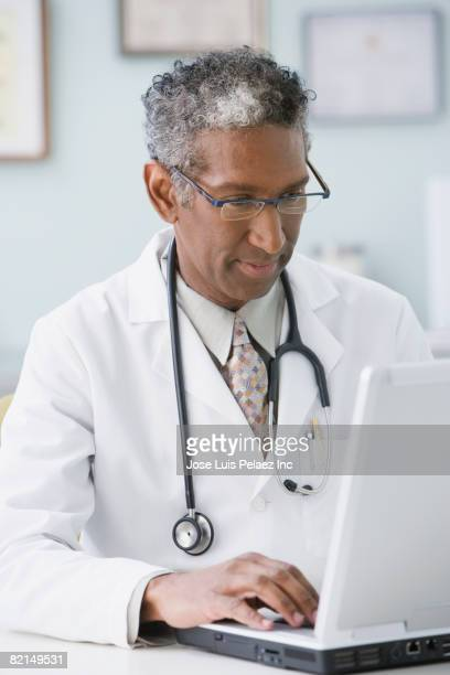 African male doctor typing on laptop