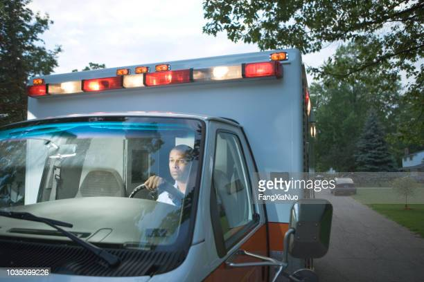 African male paramedic driving ambulance in residential area