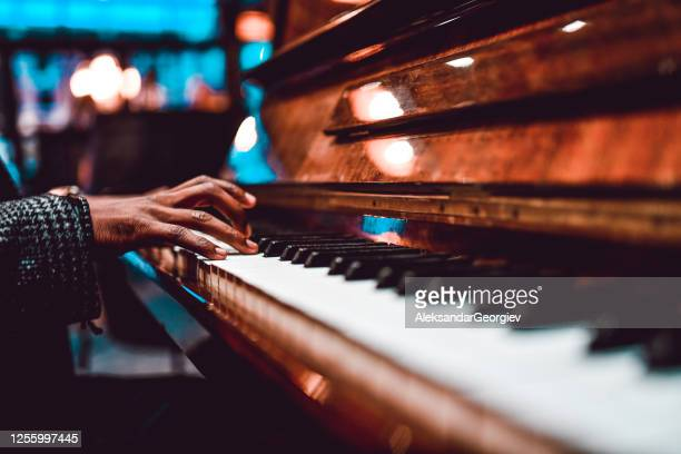 african male playing beautiful song on piano - pianist stock pictures, royalty-free photos & images