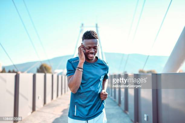 african male talking on smartphone while running on bridge - all shirts stock pictures, royalty-free photos & images
