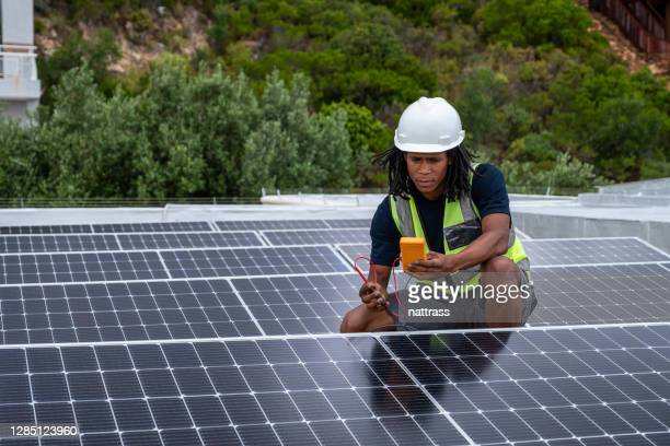 african male testing the voltage of some solar pv panels - africa stock pictures, royalty-free photos & images