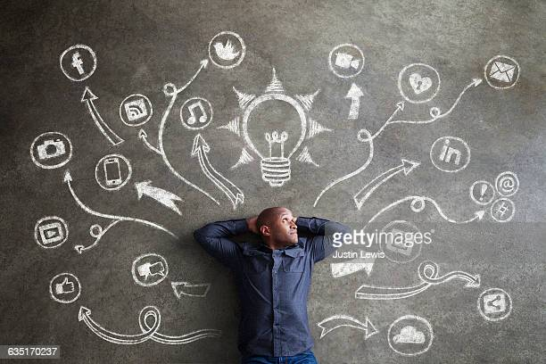 african man, 30s, surrounded by chalkboard symbols - ideas stock-fotos und bilder
