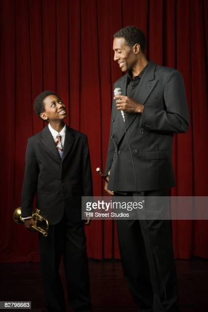African man and boy holding trumpets and microphone