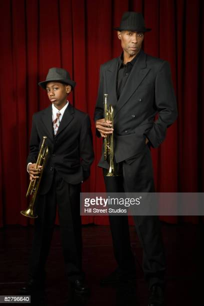 African man and boy in suits holding trumpets looking serious