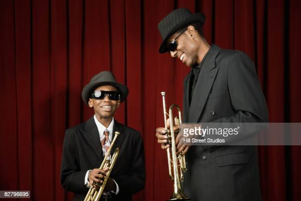African man and boy in suits holding trumpets
