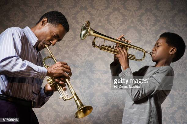 African man and boy playing trumpets