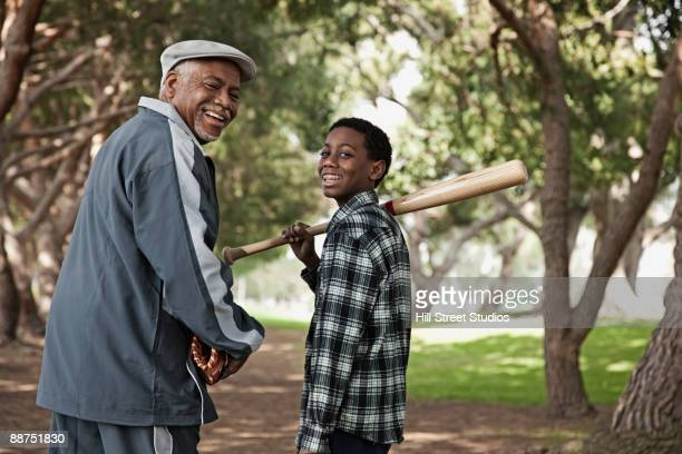 African man and grandson walking with baseball bat and glove in park
