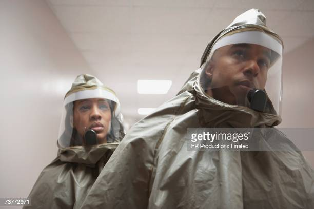 african man and woman in hazmat suits - hazmat stock pictures, royalty-free photos & images
