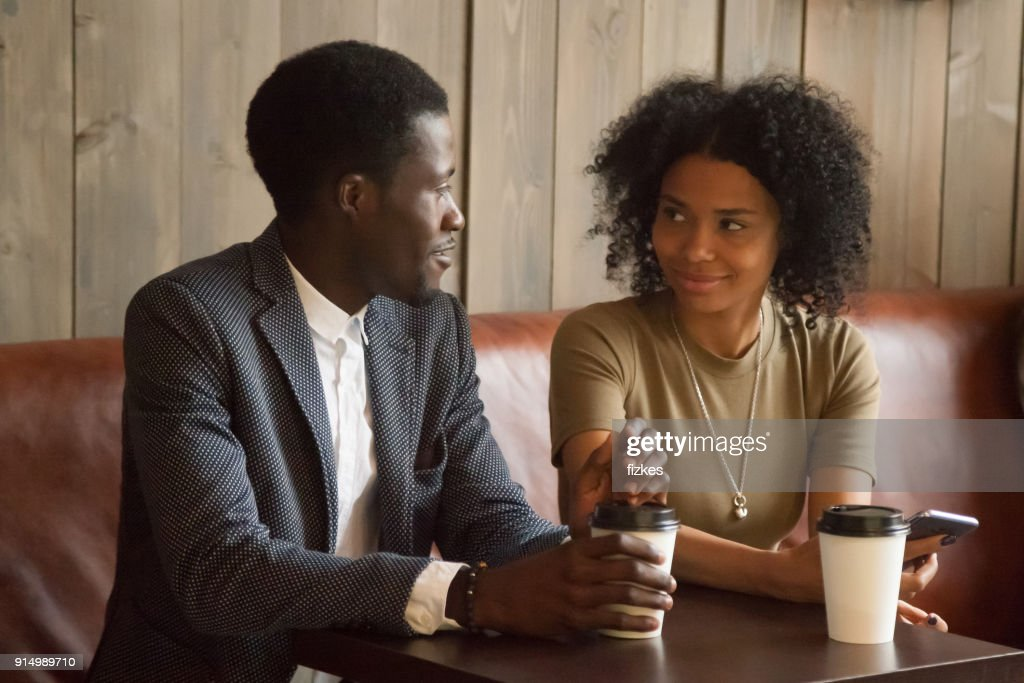 African man and woman talking flirting sitting at coffeehouse table : Stock Photo