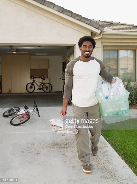 African man carrying recycling