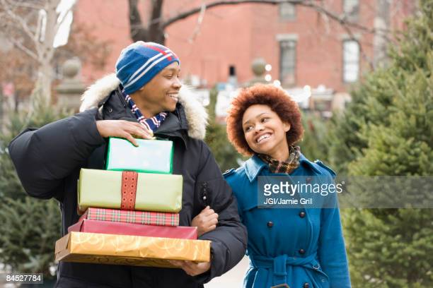 African man carrying stack of Christmas presents for girlfriend
