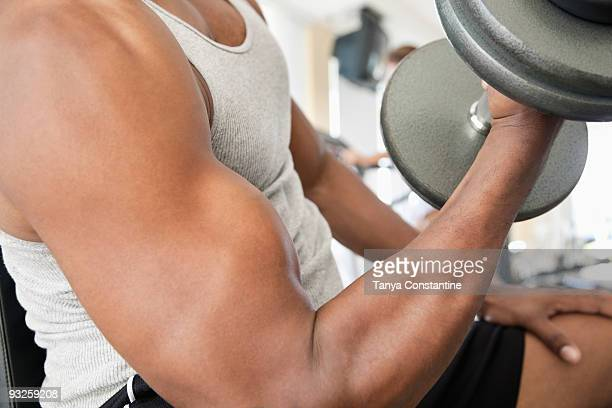 African man doing biceps curls with dumbbell