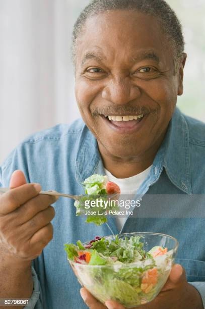 african man eating salad - one senior man only stock pictures, royalty-free photos & images