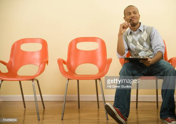 African man filling out form in waiting area