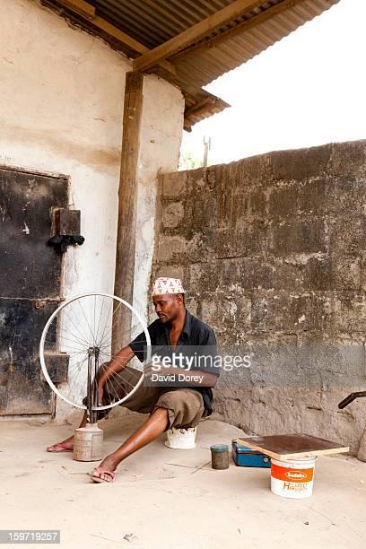 CONTENT] African man fixing a bicycle wheel Dar es Salaam Tanzania