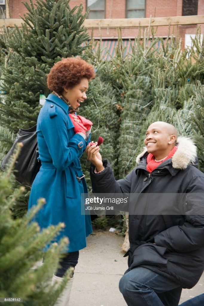 African man giving girlfriend engagement ring in Christmas tree lot : Stock Photo