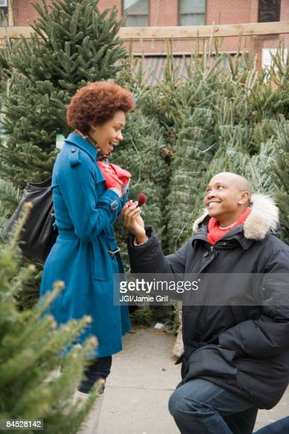 african man giving girlfriend engagement ring in christmas tree lot - black women engagement rings stock pictures, royalty-free photos & images