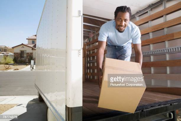 African man handing box out of back of moving truck