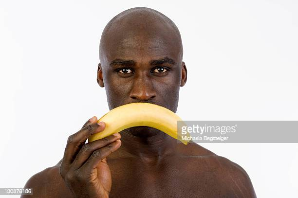 African man holding a banana in front of his mouth