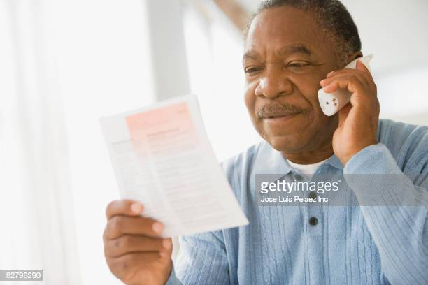 African man holding bills and talking on telephone