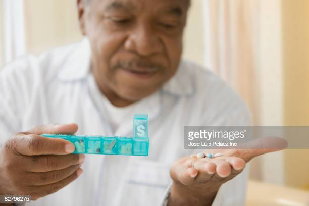 african man holding daily pill box with pills - taking a pill stock pictures, royalty-free photos & images