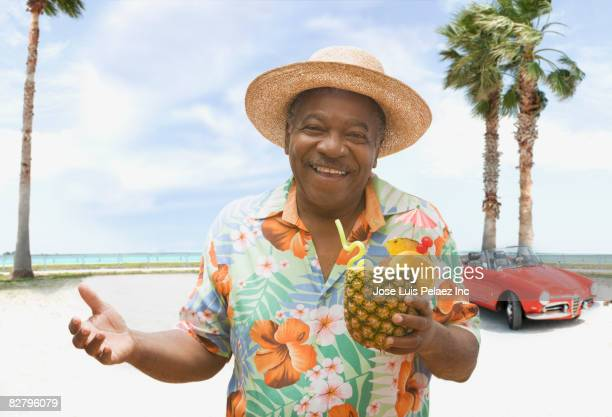african man holding pineapple drink on tropical beach - hawaiian shirt stock photos and pictures