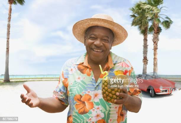 african man holding pineapple drink on tropical beach - pessoas serenas - fotografias e filmes do acervo
