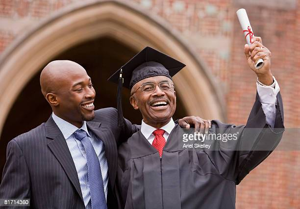 african man hugging graduate father - old university stock pictures, royalty-free photos & images