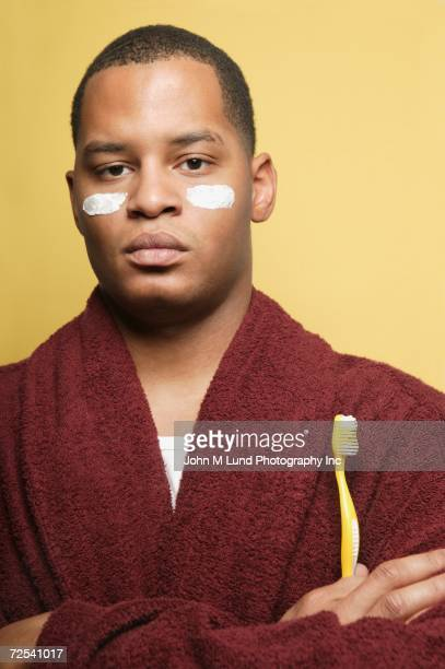 African man in bathrobe with toothbrush and white stripes on cheeks