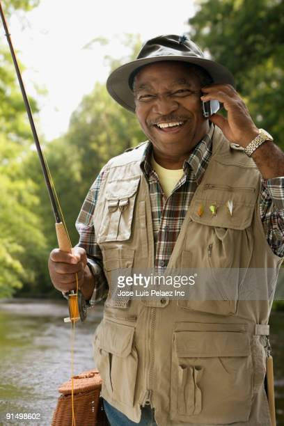 African man in fishing vest using cell phone