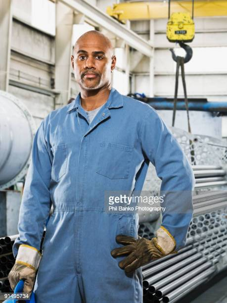 african man in gloves and coveralls in factory - black jumpsuit stock photos and pictures