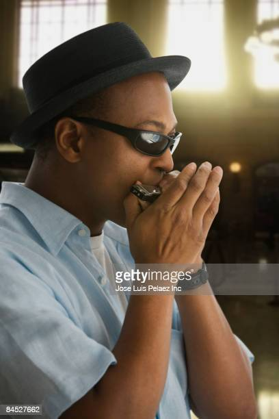 African man in hat and sunglasses playing harmonica