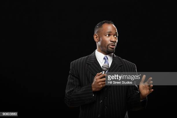 African man in suit holding microphone