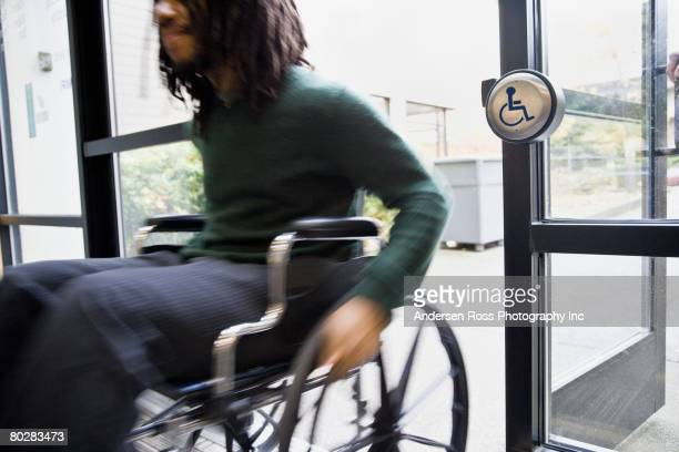 african man in wheelchair using automatic door - assistive technology stock photos and pictures