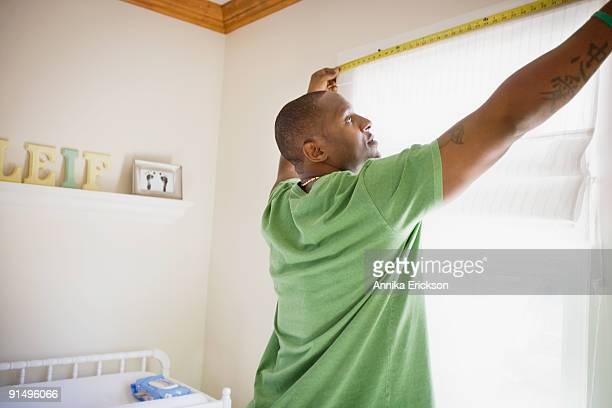 african man measuring window - measuring stock pictures, royalty-free photos & images