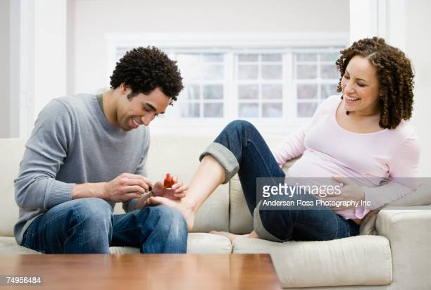 African man painting pregnant wife's toenails